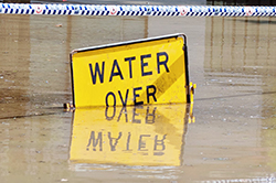 Flood water over road with sign